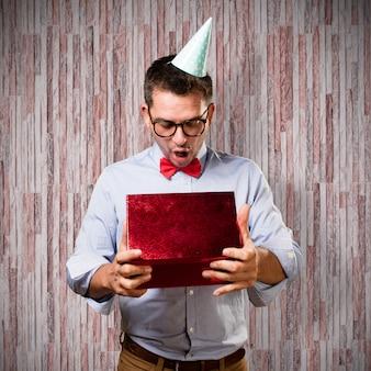 Mężczyzna ma na sobie czerwoną muszką i strona hat. gospodarstwa prezent. patrząc s