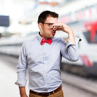 Mężczyzna ma na sobie czerwoną muszkę. robi zapach gest.