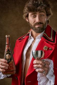 Mężczyzna ma na sobie czerwony i czarny płaszcz stojący i trzymając butelkę i kieliszek wina