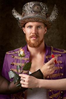 Mężczyzna ma na sobie fioletowy płaszcz i złoty kapelusz