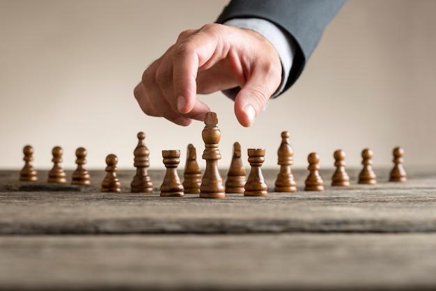 Mężczyzna ma na sobie garnitur biorąc kawałek szachy króla