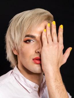 Mężczyzna ma na sobie makijaż i ma żółte paznokcie