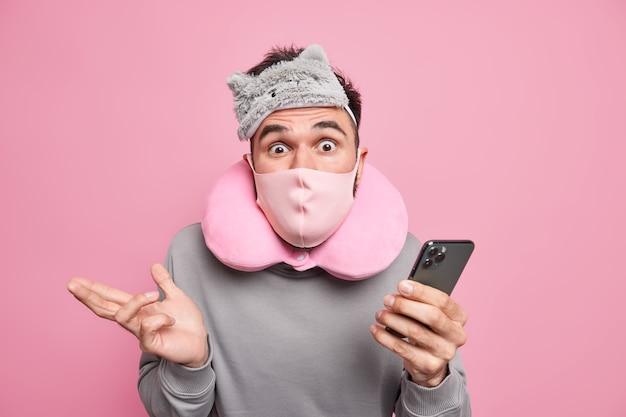 Mężczyzna ma niezrozumiały wyraz twarzy trzyma telefon komórkowy nosi maskę do spania maska ochronna na twarz poduszka na szyję