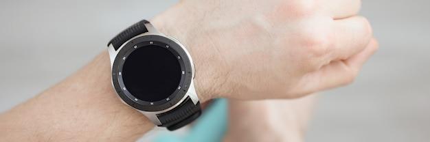 Mężczyzna ma rękę nosi inteligentny zegarek w drugiej ręce trzyma monitorowanie ćwiczeń z hantlami
