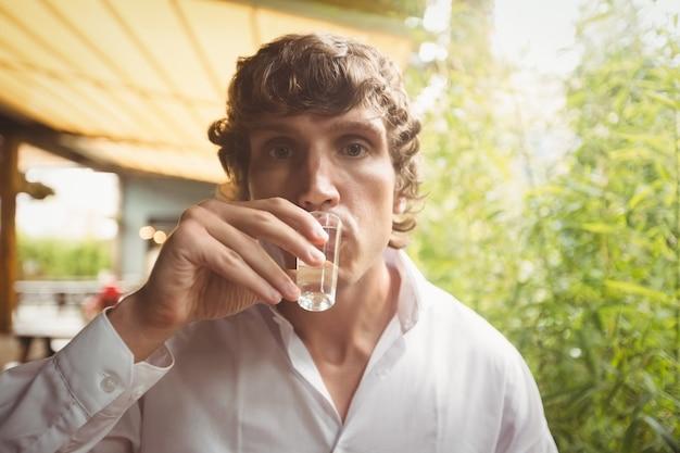 Mężczyzna ma tequila strzelającego w barze