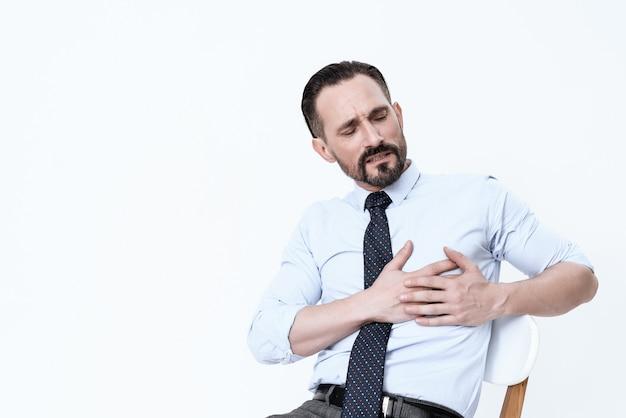 Mężczyzna ma złe serce. trzyma ręce na piersi.