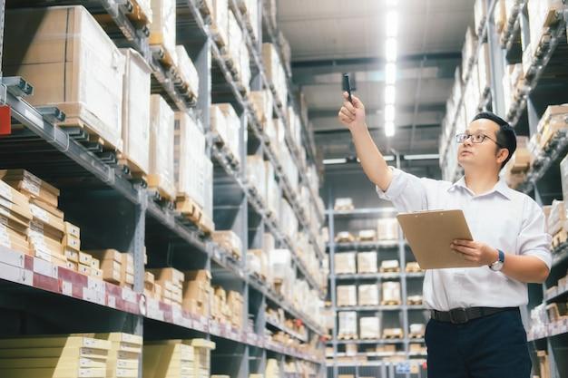 Mężczyzna magazynowy pracownik sprawdza towary przy magazynem.