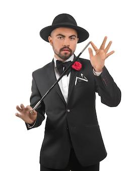 Mężczyzna magik pokazuje sztuczki na białym tle