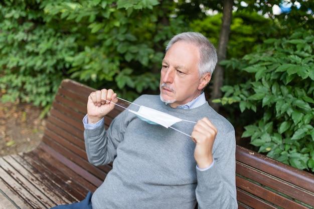 Mężczyzna mający trudności z oddychaniem w masce, zapobieganie koronawirusowi w koncepcji gorącego klimatu