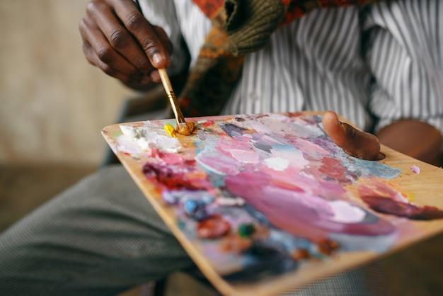 Mężczyzna malarz trzyma pędzel i kolorowe farby na palecie, studio artystyczne. artysta rysuje w swoim miejscu pracy, twórczy mistrz pracuje w warsztacie