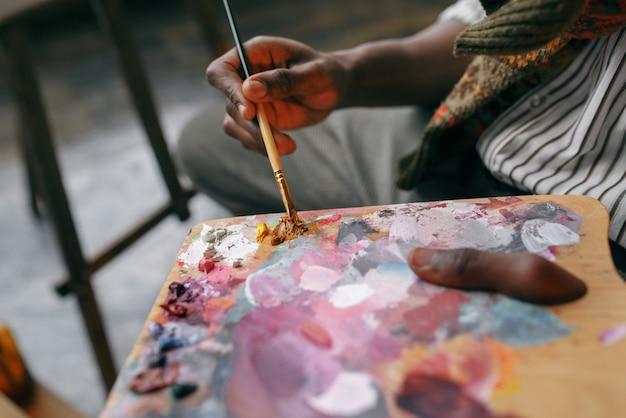 Mężczyzna malarz trzyma pędzel i kolorowe farby na palecie, studio artystyczne. artysta rysuje w swoim miejscu pracy