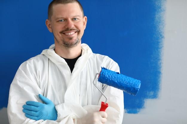 Mężczyzna malarz w mundurze z wałkiem w ręku