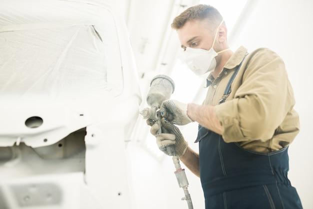 Mężczyzna malowanie auto w warsztacie