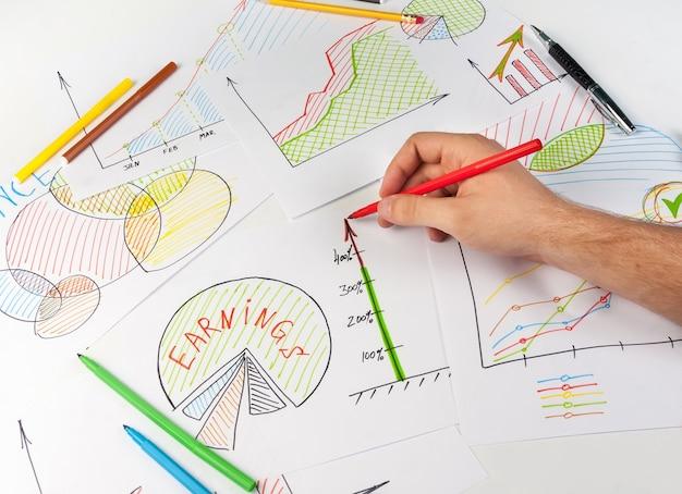 Mężczyzna malujący diagramy biznesowe na białych papierach