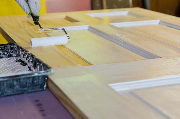 Mężczyzna malujący drewniane drzwi za pomocą wałka do malowania ze stolarzem malującym płaszcz
