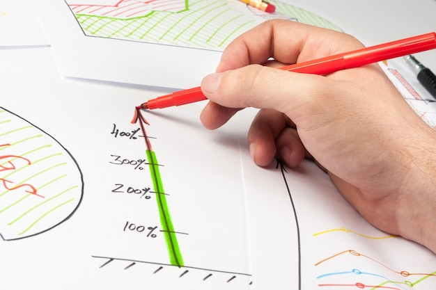 Mężczyzna maluje diagram biznesowy na białych papierach za pomocą pióra z miękką końcówką