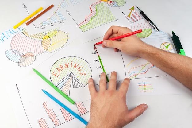 Mężczyzna maluje diagramy biznesowe na białych papierach za pomocą pióra z miękką końcówką