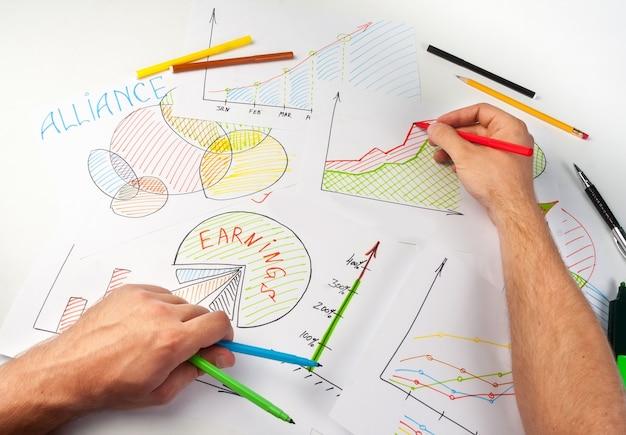 Mężczyzna maluje diagramy biznesowe na papierach za pomocą miękkiej końcówki pióra