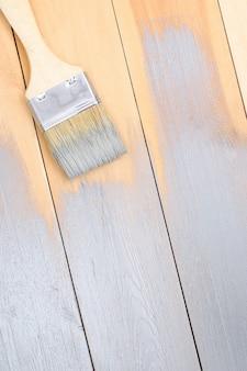 Mężczyzna maluje drewniane deski szarym pędzlem