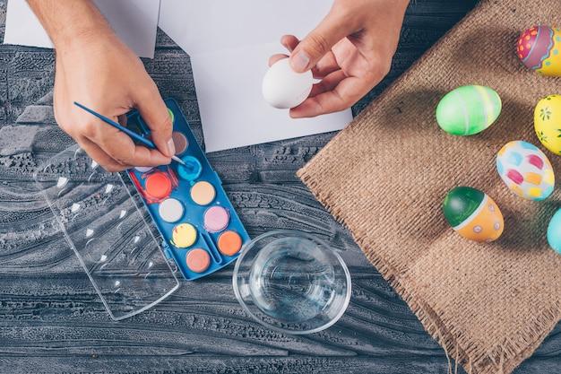 Mężczyzna maluje jajko z pisankami na worku i maluje widok z góry na ciemnym drewnianym tle