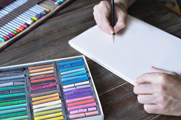 Mężczyzna maluje kredkami ołówkiem i pastelowymi kredkami