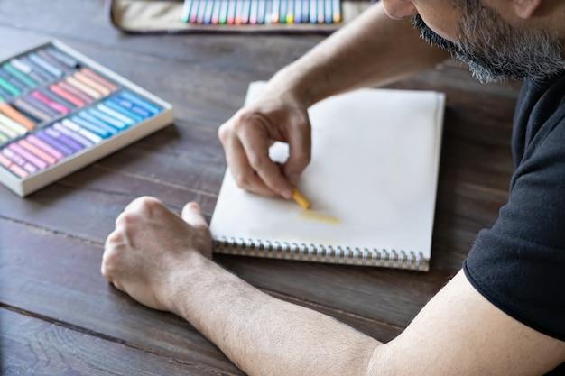 Mężczyzna maluje ołówkiem i kredkami pastelowymi na białej kartce papieru. pudełko kredek pastelowych i kredek na drewnianym stole