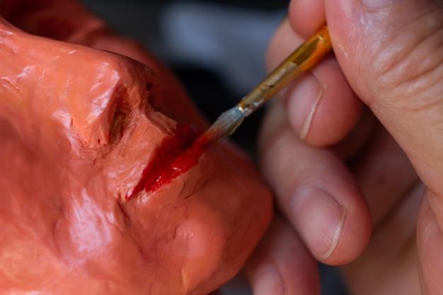 Mężczyzna maluje pędzlem usta kobiecego biustu skup się na rękodziełach kopiuj przestrzeń