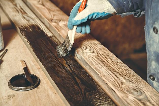 Mężczyzna maluje ręcznie robiony drewniany produkt farbą w warsztacie