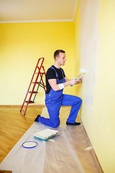 Mężczyzna maluje ścianę w domu wałkiem i farbą. remont pomieszczeń w domu.