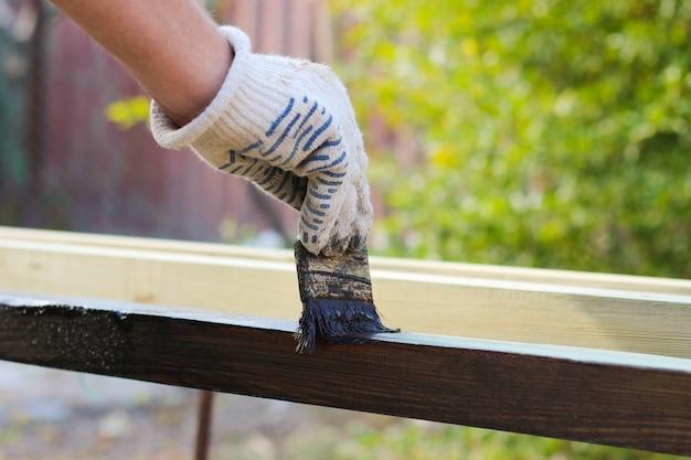 Mężczyzna maluje stare deski na farbach