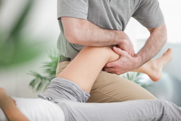 Mężczyzna manipuluje nogą kobiety, podczas gdy ona kłamie