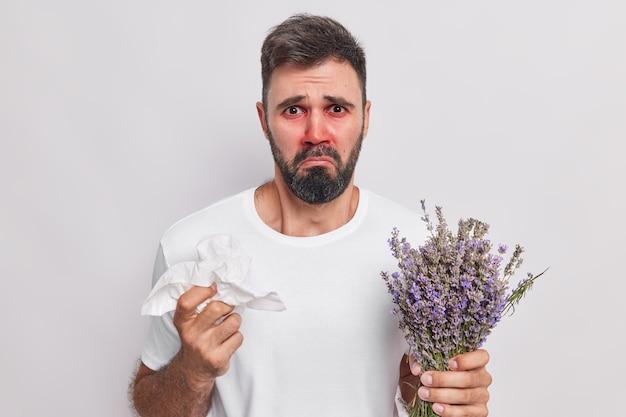 Mężczyzna marszczy brwi twarz jest niezadowolona wyraz twarzy trzyma papierową tkankę reaguje na alergen trzyma lawenda cierpi na nadwrażliwość na kwitnienie na białym tle