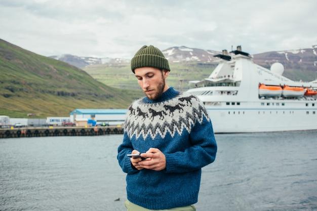 Mężczyzna marynarz w tradycyjnym swetrze stoi w porcie fiordu