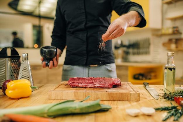Mężczyzna marynowanie surowego mięsa na desce