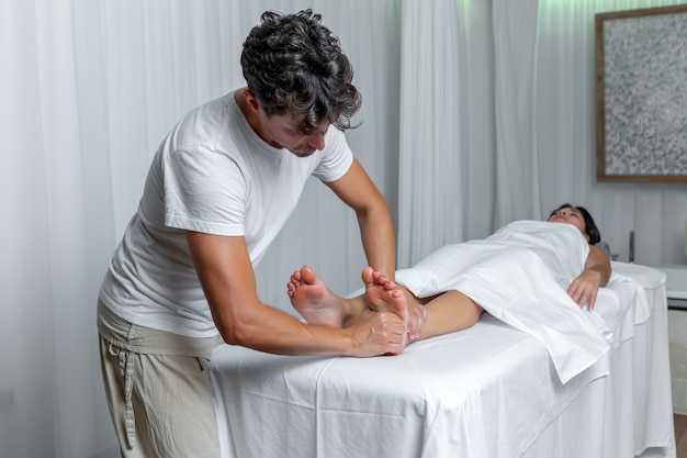Mężczyzna masażysta wywierający nacisk na stopy kobiety w masażu refleksologii w spa. koncepcja spa.