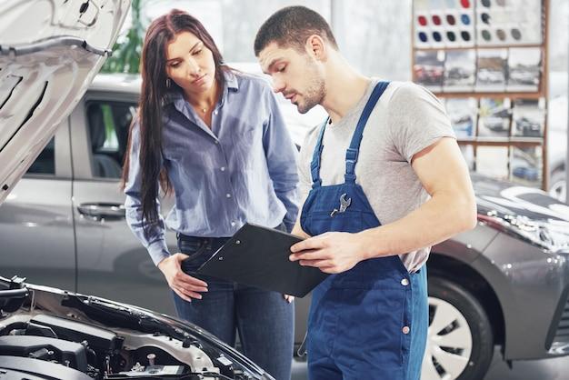 Mężczyzna mechanik i klient kobieta omawiający naprawy swojego pojazdu