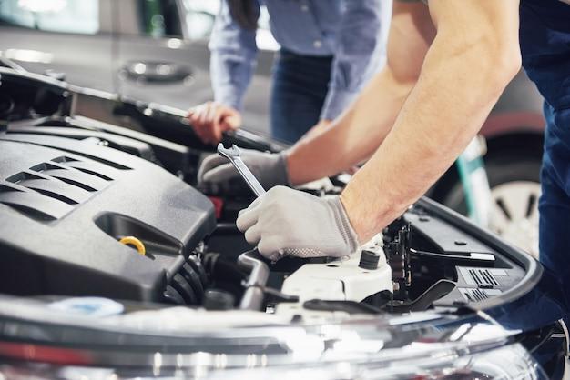 Mężczyzna mechanik i klient kobiety patrzą na maskę samochodu i omawiają naprawy
