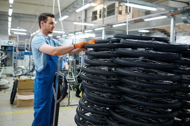 Mężczyzna mechanik na stosie kół rowerowych w fabryce. linia montażowa felg w warsztacie, montaż części rowerowych, nowoczesna technologia