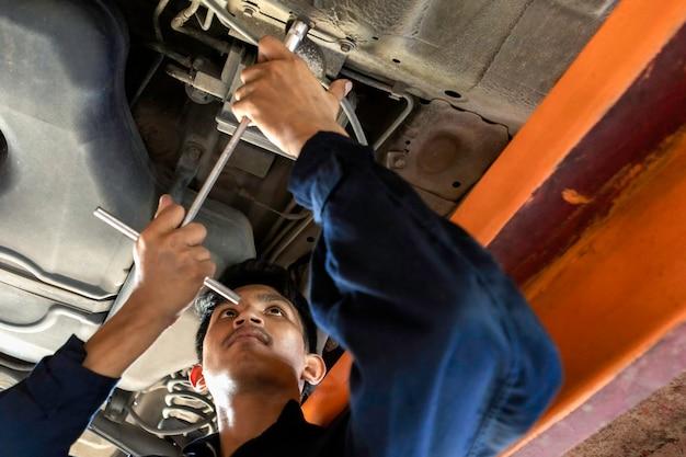 Mężczyzna mechanik naprawia silnik na podnośniku samochodowym. za pomocą narzędzi do naprawy samochodu w garażu. koncepcja samochodu serwisowego.