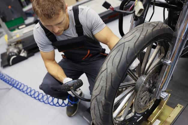 Mężczyzna mechanik pompujący opony motocyklowe w koncepcji obsługi motocykla warsztat samochodowy