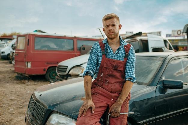 Mężczyzna mechanik pozuje na złomowisku samochodów