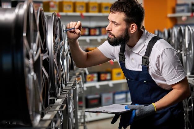 Mężczyzna mechanik samochodowy sprawdza nowe opony i tarcze w sklepie samochodowym, przygotowuje się do sprzedaży, przemysł samochodowy, brodaty mężczyzna w mundurze w miejscu pracy robi notatki