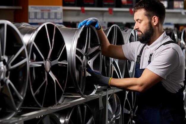 Mężczyzna mechanik samochodowy sprawdza nowe opony i tarcze w sklepie samochodowym, przygotowuje się do sprzedaży, przemysł samochodowy, brodaty mężczyzna w mundurze w miejscu pracy