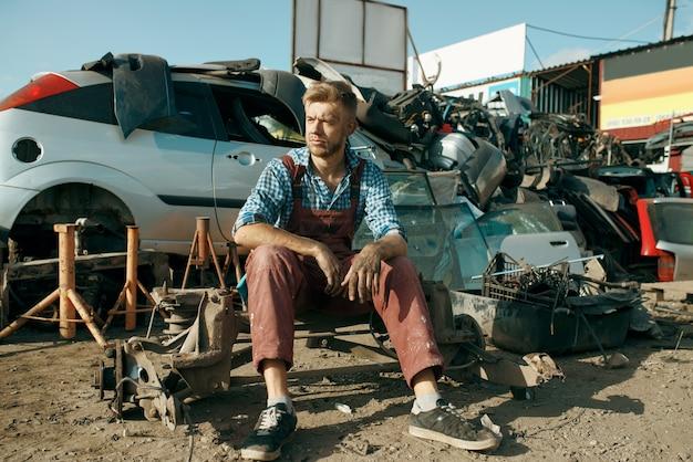 Mężczyzna mechanik siedzi na ziemi, złomowisko samochodów