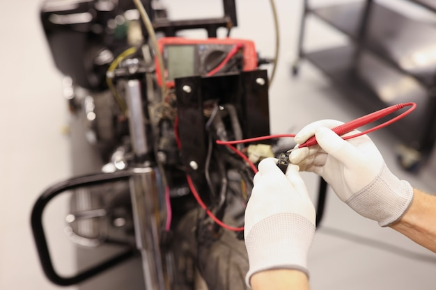 Mężczyzna mechanik sprawdzający elektrykę motocykla za pomocą testera zbliżenia nowoczesnego motocykla