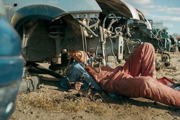 Mężczyzna mechanik w spawanie okularów na złomowisku samochodów