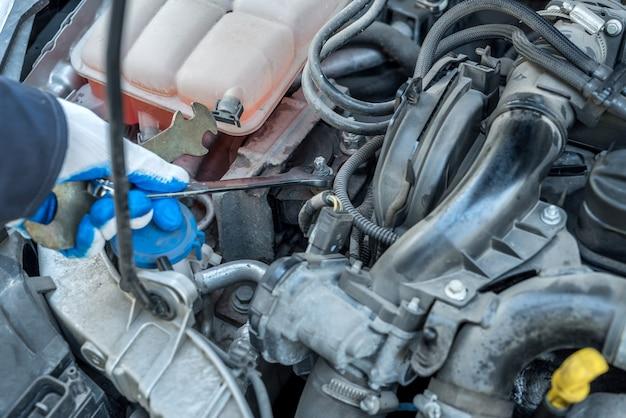 Mężczyzna mechanik za pomocą klucza klucza sprawdzanie silnika samochodu. auto serwis
