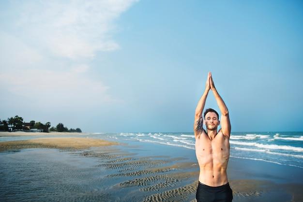 Mężczyzna medytacji plaży fitness joga koncepcja