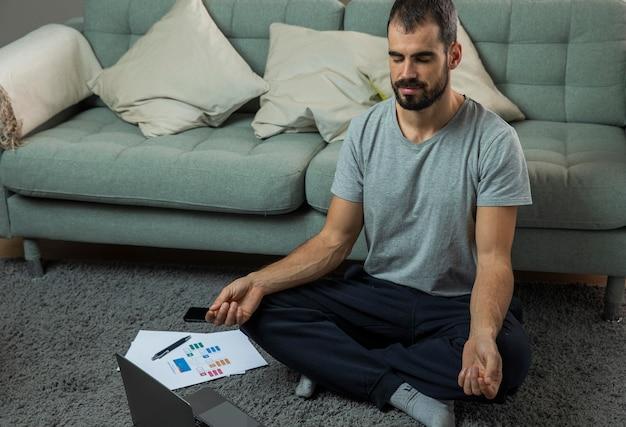 Mężczyzna medytujący obok sofy przed rozpoczęciem pracy