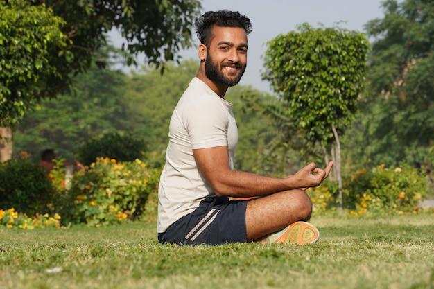 Mężczyzna medytujący siedzący ze skrzyżowanymi nogami w parku